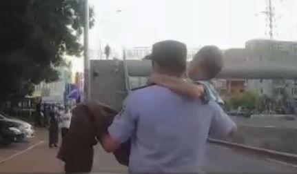 七旬老人倒路邊 民警抱著送回家